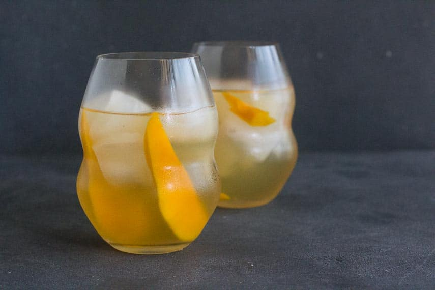 horizontal image of low FODMAP Iced White Tea with Mango in decorative clear glasses on dark background