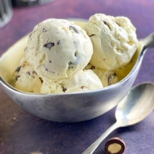 horizontal image of silver dish of low FODMAP No Churn Vanilla Ice Cream with Chocolate Covered Almonds on purple backdrop