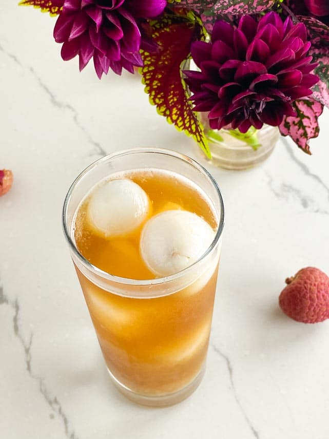 looking down into glass of Low FODMAP Iced Black tea with Lychees on white marble table
