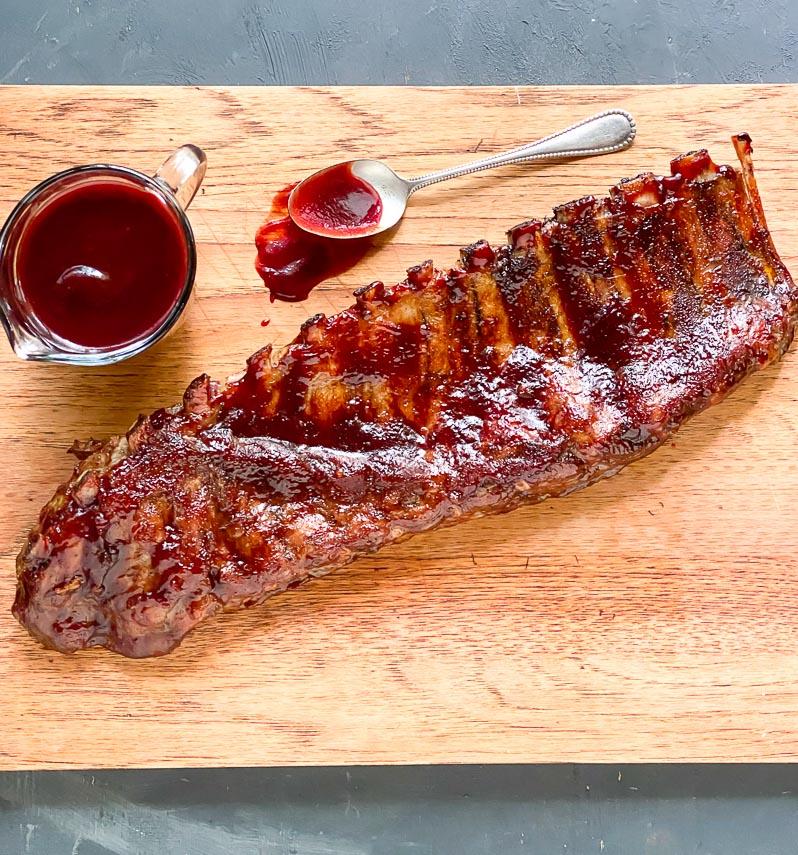 low FODMAP Blackberry Maple BBQ Ribs on wooden board; extra sauce alongside