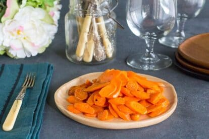 low FODMAP sauteed carrots on wooden plate; wine glass in background