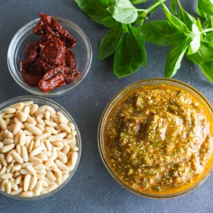 overhead view of low FODMAP sun-dried tomato pesto in glass bowl; pine nuts and basil alongside on dark surface