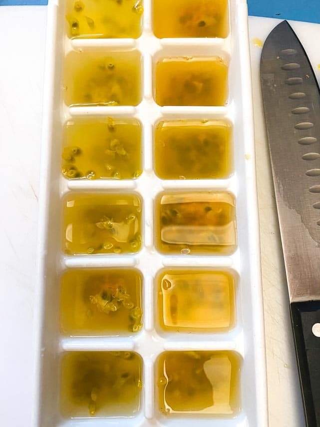 passionfruit flesh and seeds spooned into ice cube tray; filled with water ready to be frozen