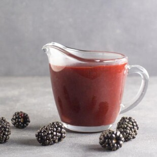 side view of low FODMAP Blackberry Maple BBQ Sauce in clear pitcher, dark table