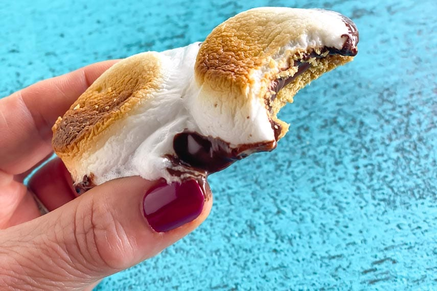 s'mores held in hand over aqua surface