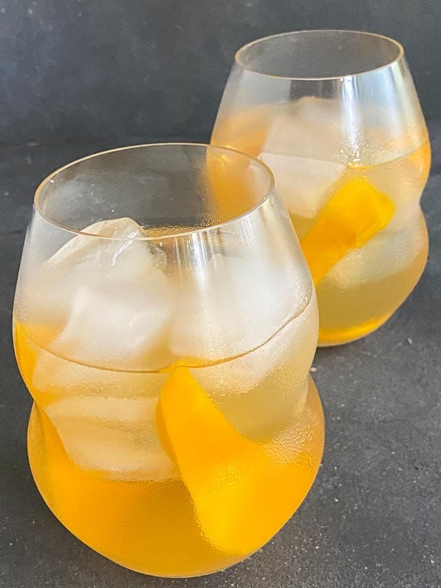 two glasses of low FODMAP Iced White Tea with Mango in decorative clear glasses on dark background