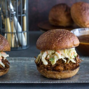 two low FODMAP BBQ Pork Sliders on a metal tray; sauce in background in glass dish