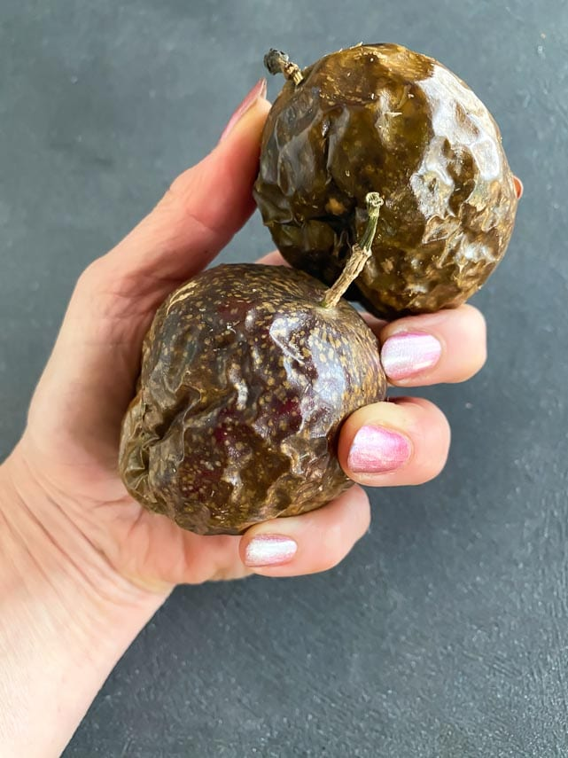 two ripe passionfruit held in hand_