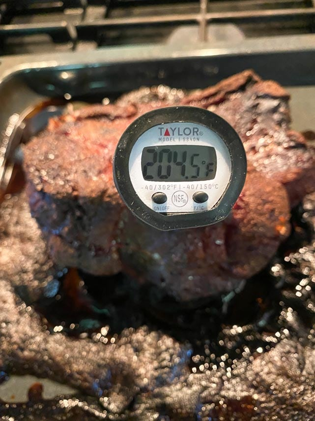 using an instant read thermometer in pork shoulder, showing 204°F