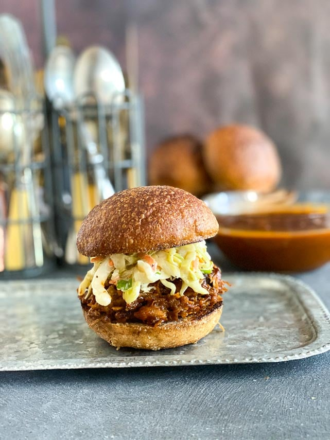 vertical image of Low FODMAP BBQ Pork Slider on a metal tray; extra sauce in glass dish in background