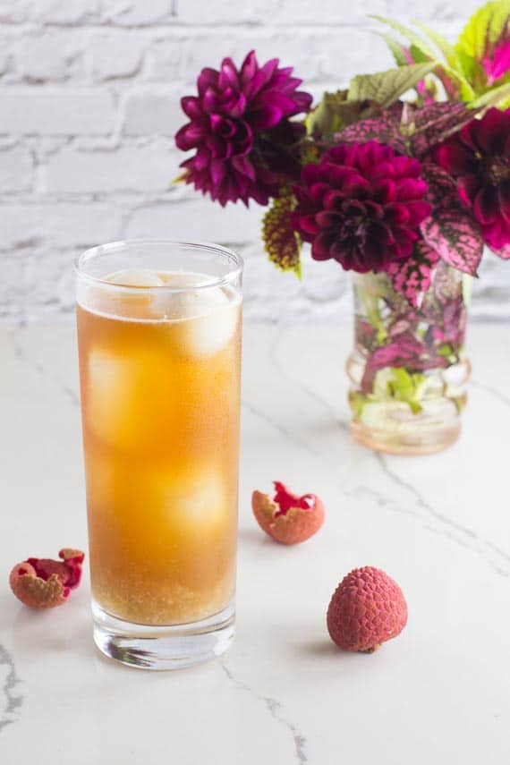 vertical image of Low FODMAP Iced Black tea with Lychees in tall clear glass; white background and magenta flowers in a small vase