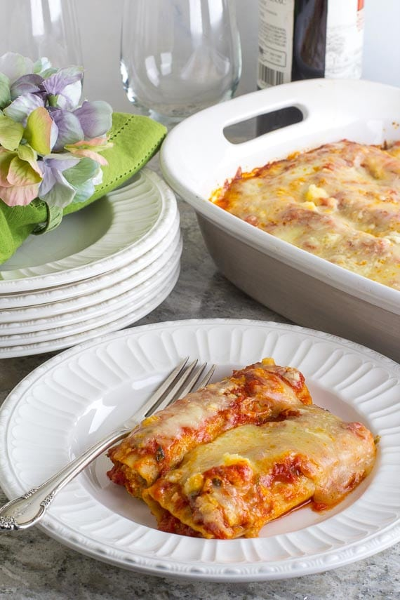 vertical image of Low FODMAP Manicotti on a white plate with silver fork; green napkin
