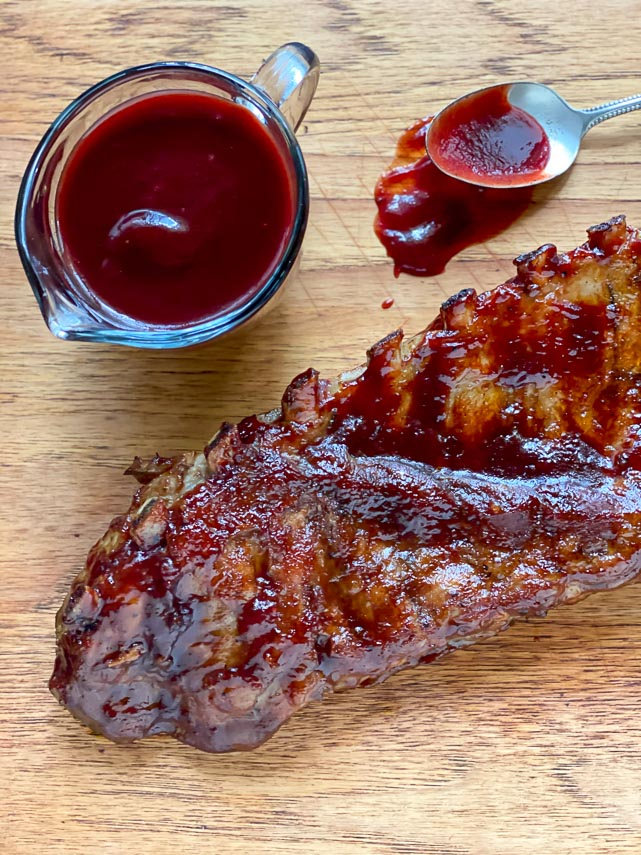 vertical image of glazed ribs on wooden board