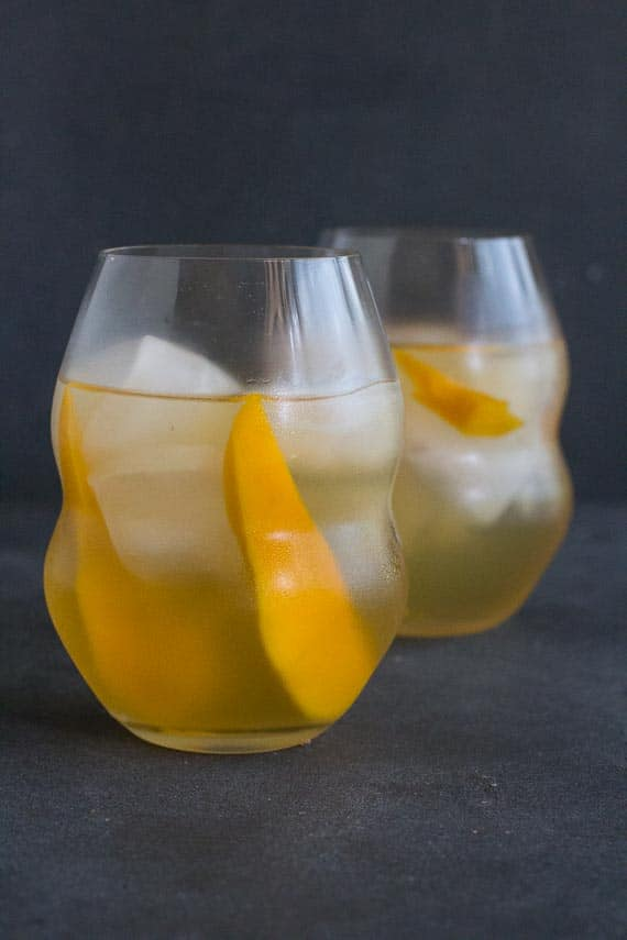 vertical image of low FODMAP Iced White Tea with Mango in decorative clear glasses on dark background