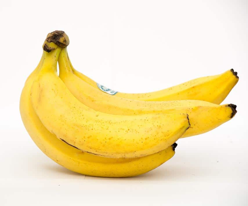 Bunch of ripe bananas showing an even yellow color and no green at all. Black spots beginning to appear copy