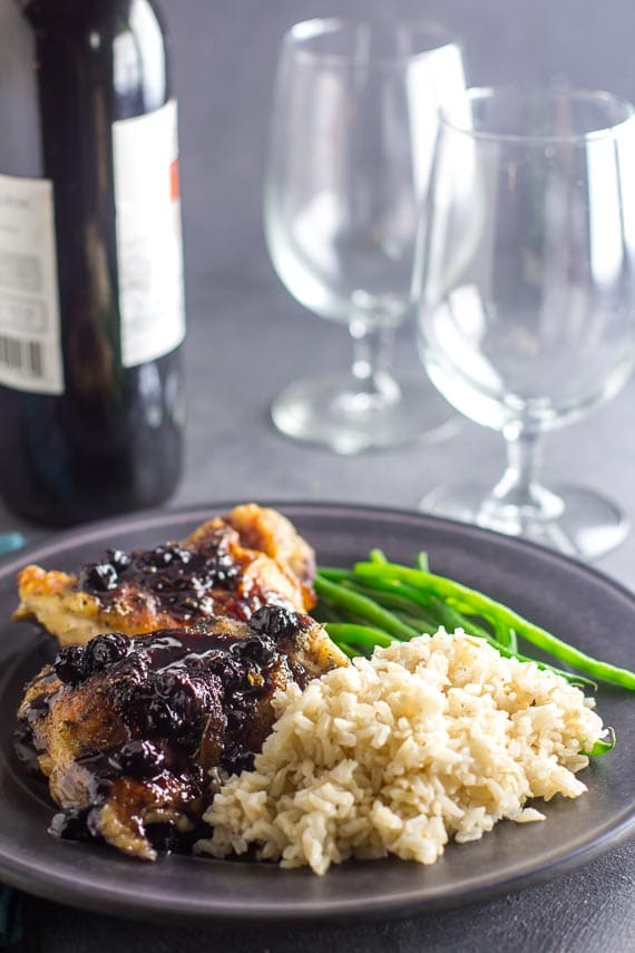 Chicken With Roasted Blueberries on gray plate with rice and green beans; wine glasses in background