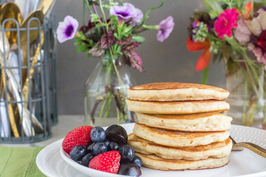 Fluffy pancakes, waiting for syrup, on a white plate with fruit on the side