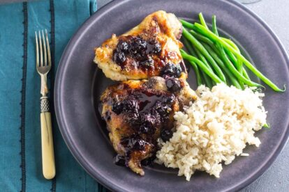 Low FODMAP Maple Balsamic Chicken With Roasted Blueberries on gray plate with rice and green beans; antique fork alongside