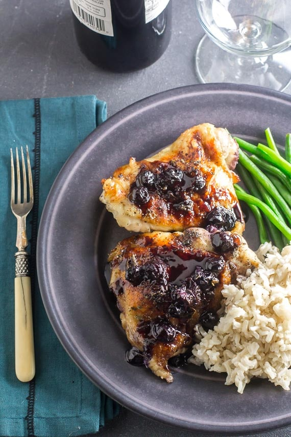 Low FODMAP Maple Balsamic Chicken With Roasted Blueberries on gray plate with rice and green beans