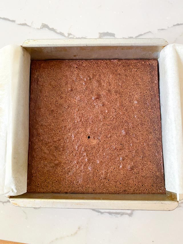 baked brownies in square pan showing tiny hole where I tested for doneness