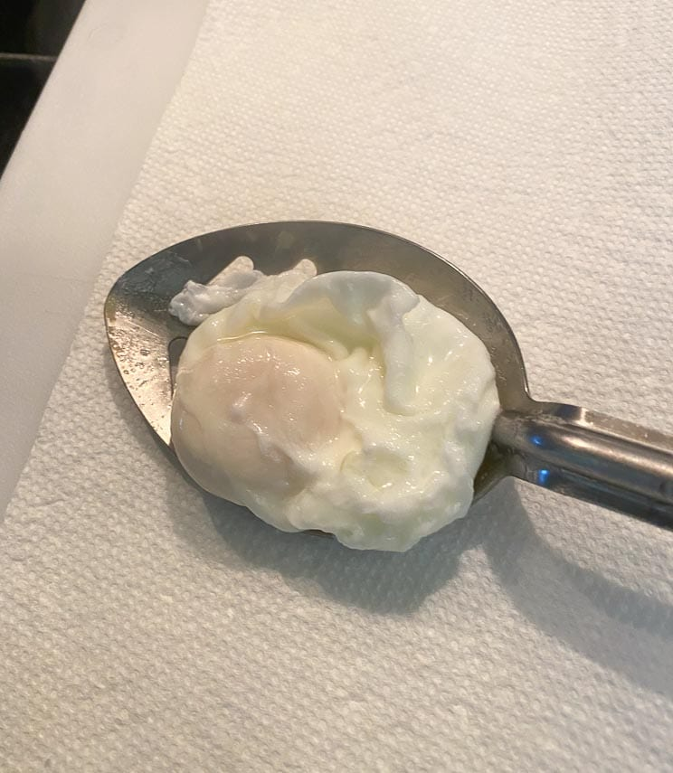blotting poached egg on paper towel still in slotted spoon