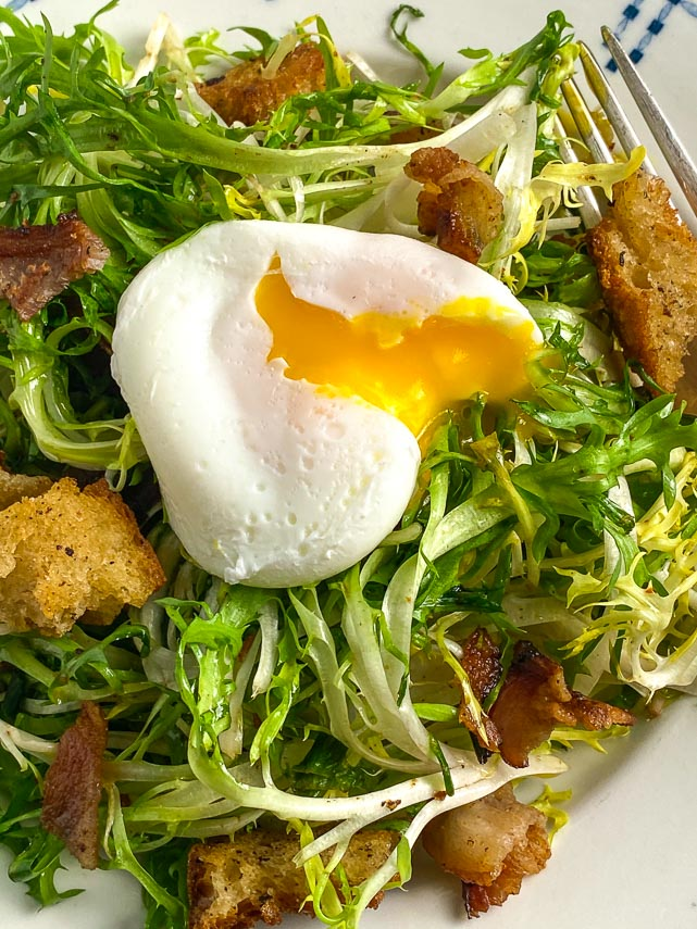 broken open poached egg on top of frisee salad