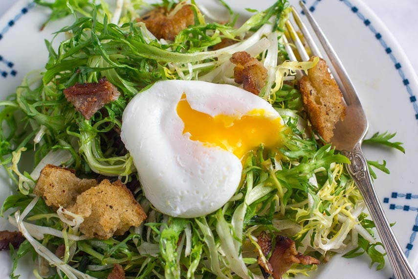 closeup of frisée salad with poached egg, bacon and sourdough croutons in white plate with blue border; silver fork alongside