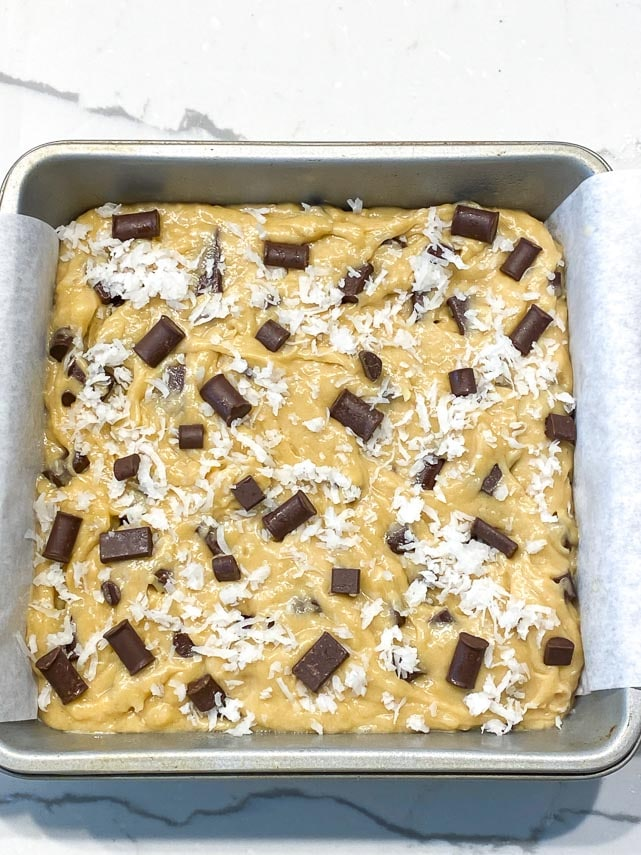 cookie dough blondie batter spread into square baking pan lined with parchment
