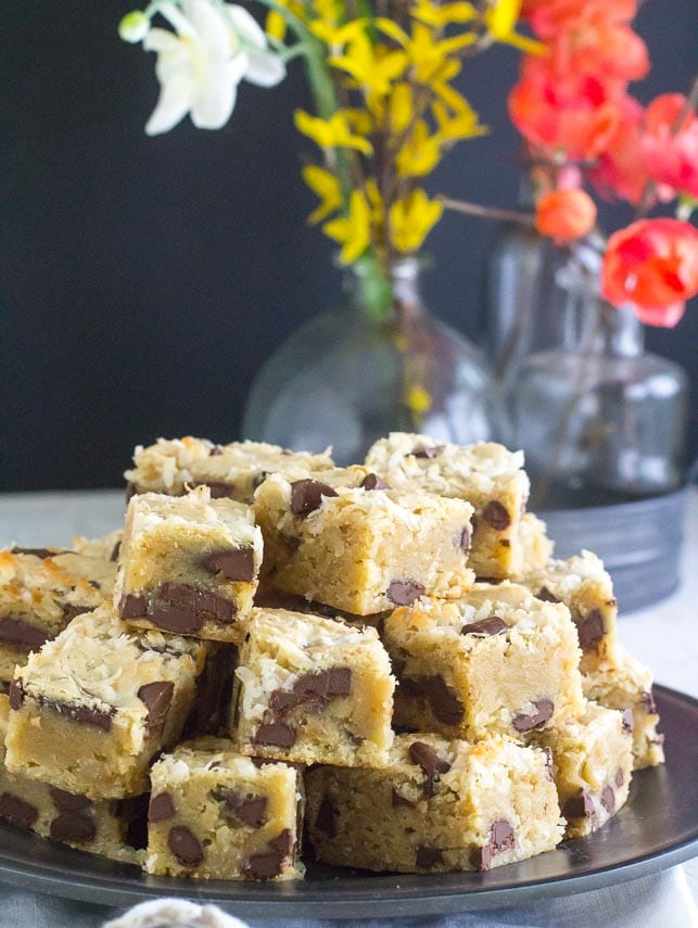 cookie dough blondies on a black plate on white painted surface; flowers in background-2