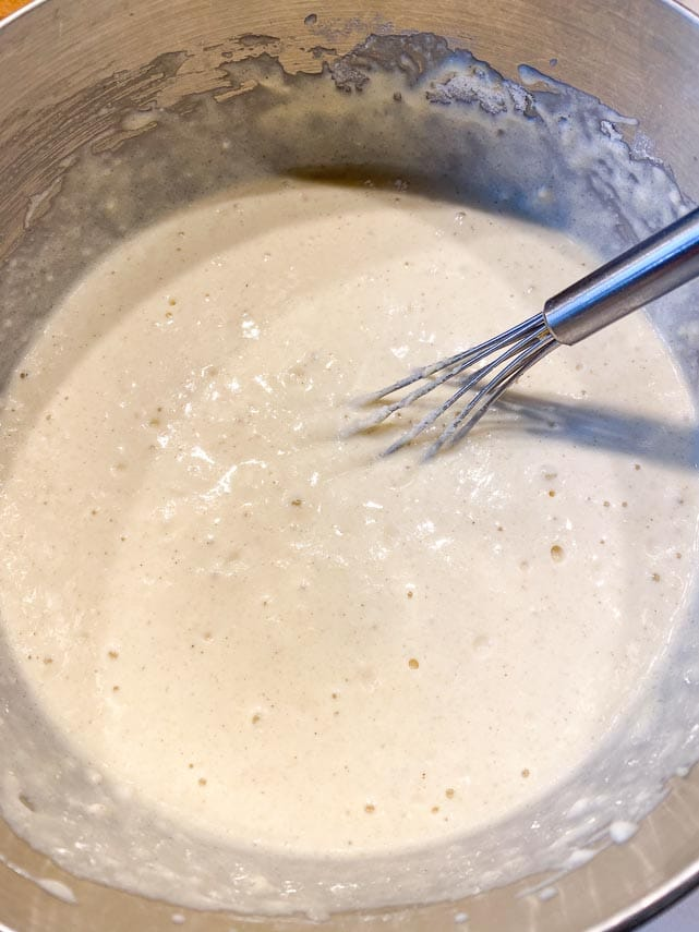 fluffy pancake batter in mixing bowl with whisk