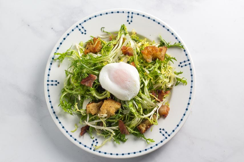 frisée salad with poached egg on white plate with blue border