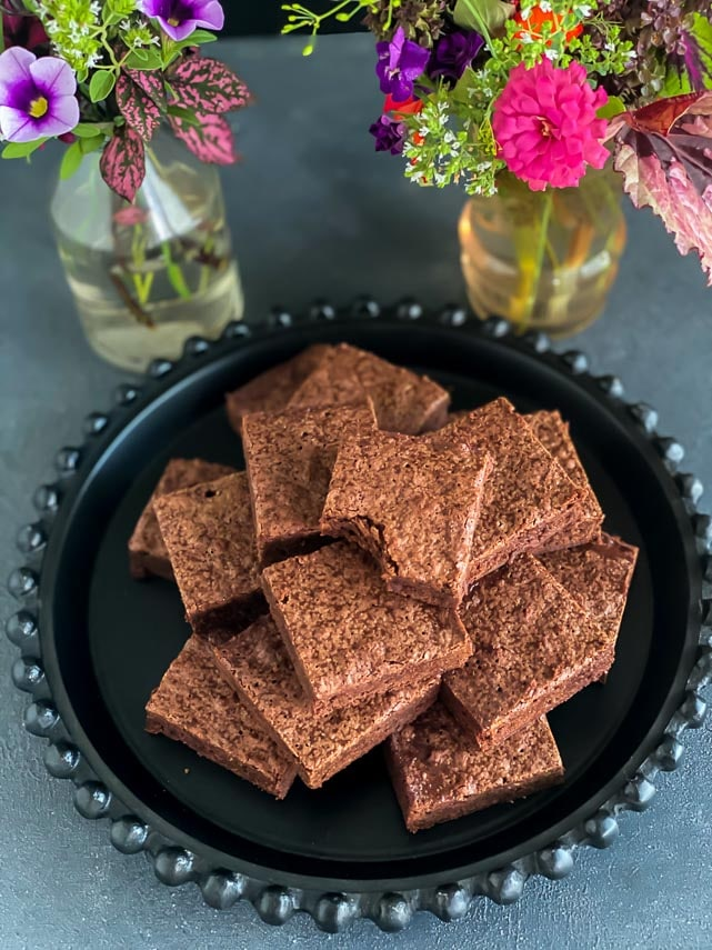 low FODMAP One Bowl Brownies piled on black plate; fresh flowers in background