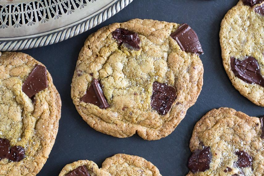 low FODMAP Salted Buckwheat Chocolate Chunk Cookies on a dark surface; silver tray showing in corner