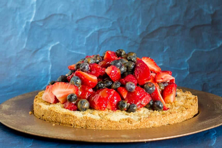 low FODMAP hazelnut shortcake topped with mixed berries against blue background