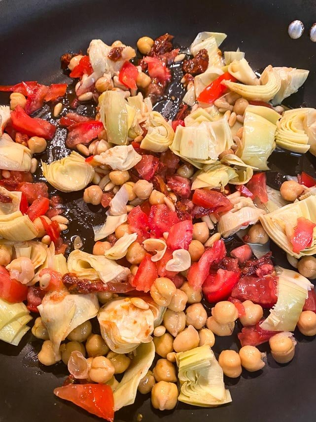 making pasta with sun-dried tomatoes, chickpeas and artichokes in pan