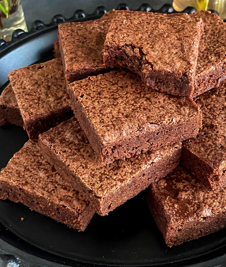 one bowl brownies in a pile on a black plate