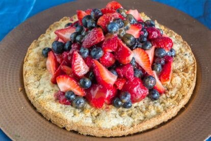 overhead hazelnut shortcake on brass platter with berries