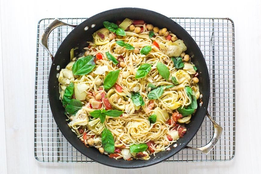 overhead image of pasta dish with chickpeas, tomatoes and artichokes in a pan on a cooling rack