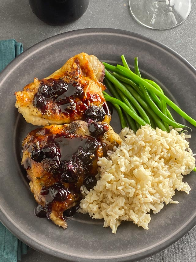 overhead image of roastd chicken with blueberries; rice and green beans on gray plate