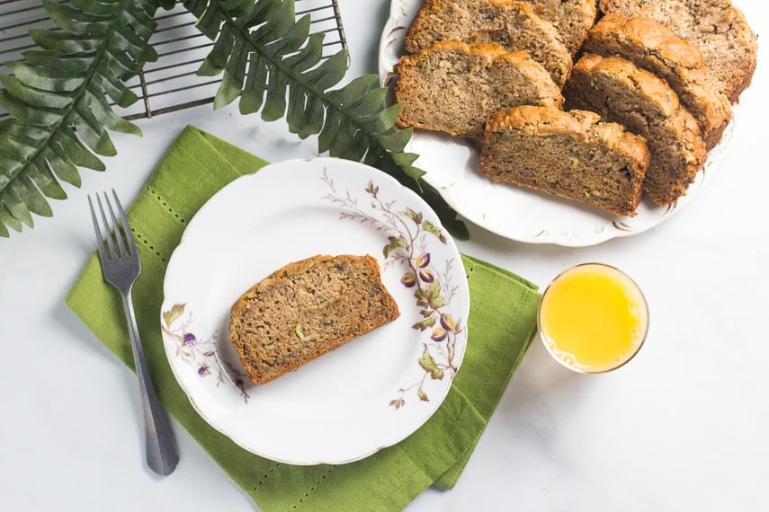 overhead of slice of zucchini banana bread on white bread; glass of orange juice alongside and fork and green napkin