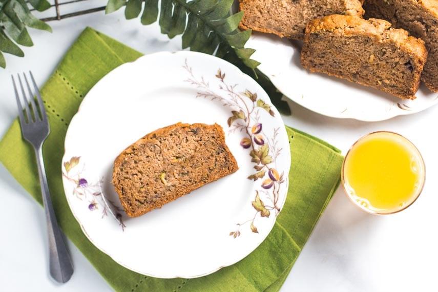 overhead of slice of zucchini banana bread on white bread; glass of orange juice alongside