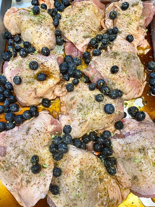 raw chicken and blueberries in roasting pan
