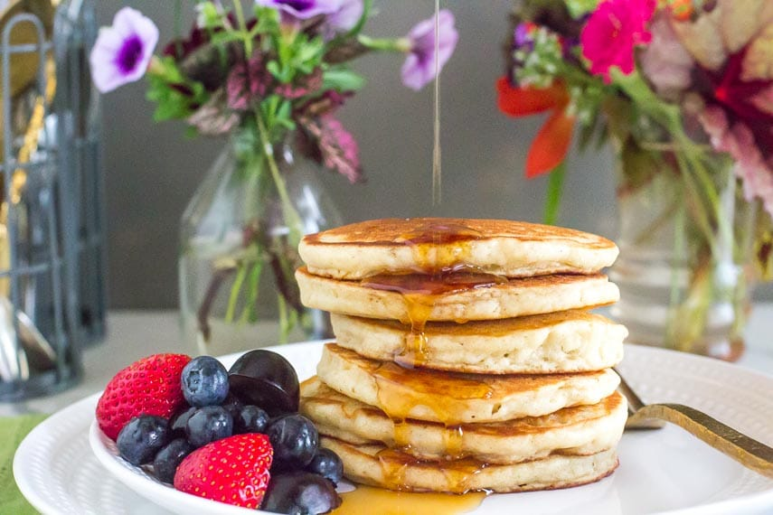 stack of fluffy pancakes on white plate with syrup being poured on top; fruit on the side