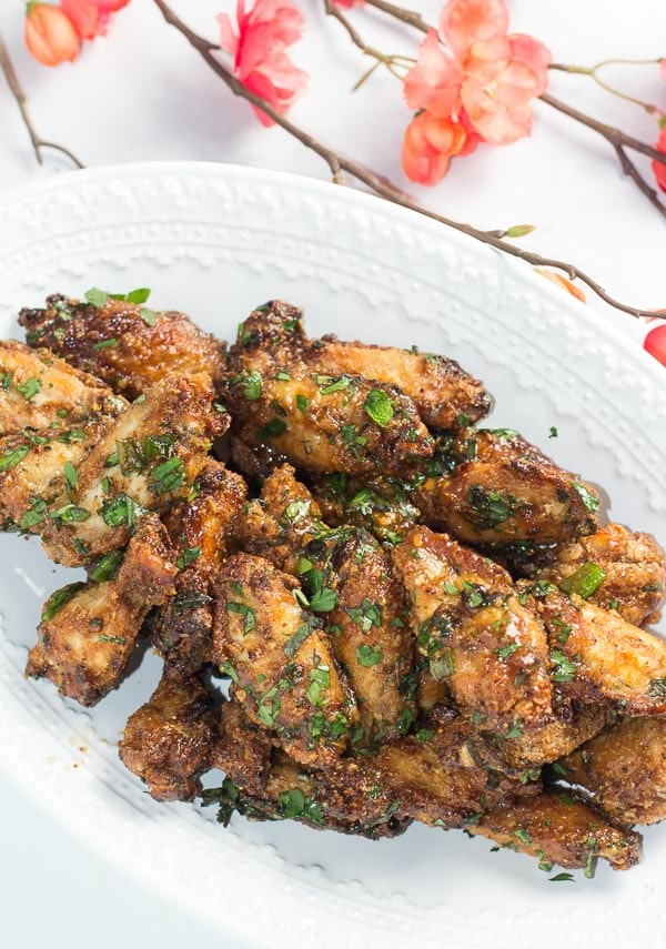 vertical image of Low FODMAP Pok Pok Chicken Wings on oval white plate with coral colored flowers in background