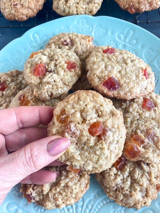 vertical image of oatmeal cookies held in manicured hand over aqua plate