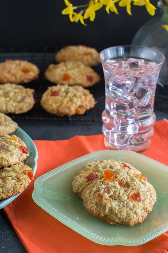 vertical image of oatmeal cookies on square green plate on top of orange napkin