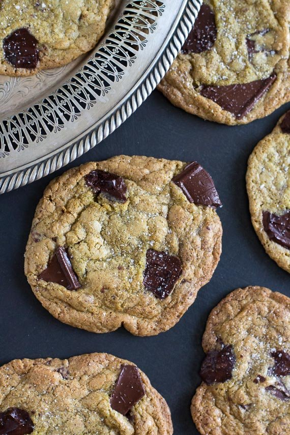vertical image of salted buckwheat chocolate chunk cookies on dark background