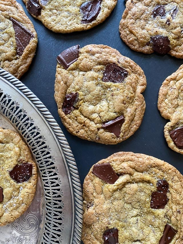 vertical image of salted chocolate chunk cookies on dark background