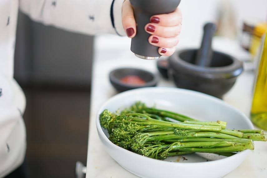 woman preparing broccolini in a white bowl