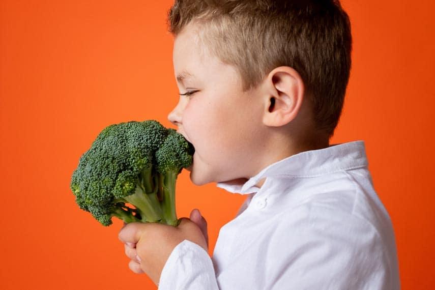 young boy enjoying raw broccoli